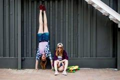 Två nätta le blonda flickor som bär rutiga skjortor, lock och grov bomullstvillkortslutningar, balanserar framme av den svarta vä royaltyfria bilder
