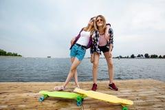 Två nätta le blonda flickor som bär rutiga skjortor och grov bomullstvillkortslutningar, står på pir och har gyckel med fotografering för bildbyråer