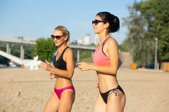 Två nätta medelåldersa kvinnliga joggers som bär solglasögon och baddräktutbildning på stranden arkivfoton