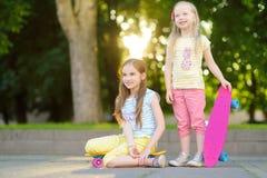 Två nätta små flickor som lär till skateboarden på härlig sommardag i en parkera Barn som utomhus tycker om skateboarding ritt Arkivbilder