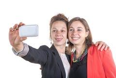 Två nätta tonåriga flickor som tar selfies med hennes smarta telefon Royaltyfria Foton
