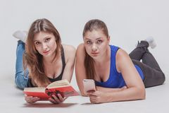 Två nätta unga kvinnor lägger på golvet med boken och mobiltelefonen royaltyfri fotografi