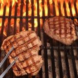 Två nötköttbiffar på det varma flammande gallret för BBQ Arkivfoto