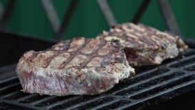 Två nötköttbiffar som grillas på kol stock video