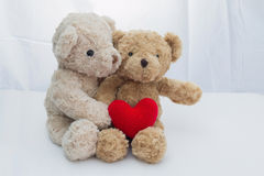 Två nallebjörnar som sitter med rött hjärtagarn på vitt tyg arkivbilder