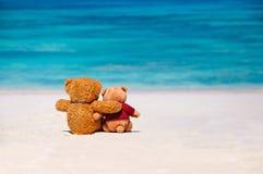 Två nallebjörnar som sitter på stranden Fotografering för Bildbyråer