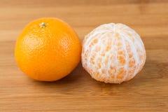 Två navelapelsiner en skalade unpeeled en Royaltyfri Fotografi