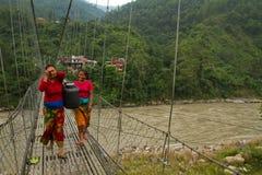 Två Nepalikvinnor och en bro i Chitwan, Nepal Fotografering för Bildbyråer