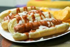 Två New York stilvarmkorvar med ketchup, senap, lökar och en sida av potatischiper, tjänade som på en vitbokplatta arkivfoto