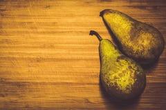 Två nya päron som inte skalas på ett träbräde Vitamin sund mat fotografering för bildbyråer