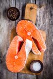 Två nya rå laxbiffar på en skärbräda med salt och peppar Fotografering för Bildbyråer