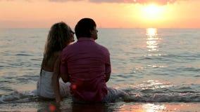 Två nygifta personer som sitter på stranden stock video