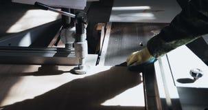 Två oigenkännliga snickare eller föreningsmänniskor använder en ny skarp cirkelsåg för att klippa träflismaterialet arkivfilmer