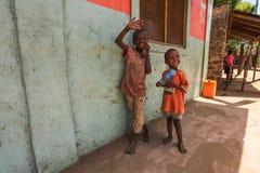 Två okända lilla pojkar och att stå bredvid väggen, le och vinkande till den turist- besöka lokala slumkvarteret Många barn lider royaltyfri foto