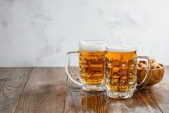 Två Oktoberfest öl med pistaschmuttrar på en träbakgrund royaltyfri fotografi