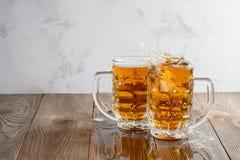 Två Oktoberfest öl plaskar på en träbakgrund arkivfoton