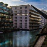 Två olika byggnader på bankerna av floden Royaltyfri Fotografi