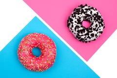 Två olika donuts på mångfärgad bakgrund fotografering för bildbyråer