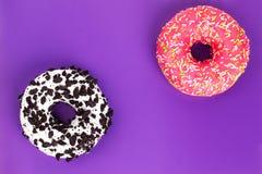 Två olika donuts på purpurfärgad bakgrund royaltyfria bilder