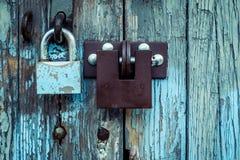 Två olika lås på den mycket gamla trägaragedörren som skalar smärtar arkivbild