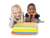 Två olika lilla skolbarn med deras böcker Fotografering för Bildbyråer