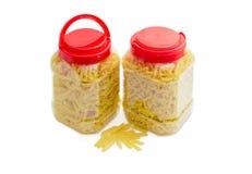 Två olika plast- behållare för pasta itu med röda räkningar Arkivfoton