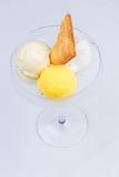 Två olika skopor av glass med kakan och passionfrukt i ett exponeringsglas Royaltyfri Bild