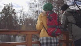 Två omslag och hattar för lyckliga turister som iklädda står på bron nära flodsamtalet och att tycka om naturen Semestra av stock video