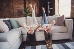 Två optimistiska flickor för trevlig älskvärd attraktiv sund gladlynt glad vänskapsmatch som ligger på den uppochnervända soffan  royaltyfria foton