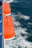 Två orange livfartyg på en färja på havet Arkivfoto