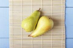 Två organiska päron på matt bambu Bästa sikt på trätabellen Ny frukt för sund frukost eller matställe royaltyfri bild