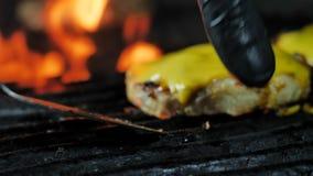 Två ostsmå pastejer för grillade hamburgare smältte ost på en kotlett; smältt brand i bakgrunden, ultrarapid stock video