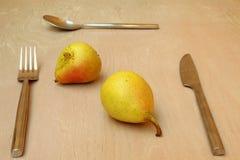 Två päron och bestick (sked, kniv och gaffeln) Arkivfoto