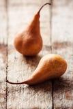 Två päron på en lantlig träbakgrund Arkivfoto