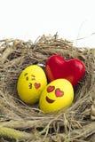 Två påskägg målade med emojis, en som var förälskad, och annan kissi Arkivfoton
