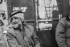 Två palestinska män sitter ha en pratstund zigarettes i t royaltyfri foto