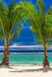 Två palmträd över att bedöva den blåa lagun, kock Islands Arkivbild