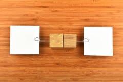 Två pappers- anmärkningar med hållare i olika riktningar på trä Royaltyfri Fotografi