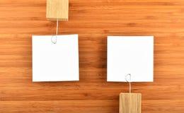 Två pappers- anmärkningar med hållare i olika riktningar på trä Royaltyfri Foto