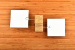 Två pappers- anmärkningar med hållare i olika riktningar på trä Royaltyfria Bilder