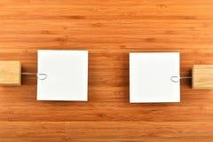 Två pappers- anmärkningar med hållare i olika riktningar på trä Arkivfoto