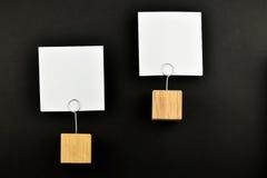 Två pappers- anmärkningar med hållare på svart för presentation Royaltyfria Foton