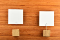 Två pappers- anmärkningar med trähållare på träbakgrund Arkivbild