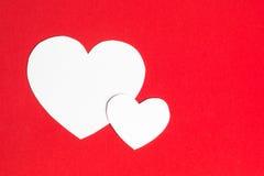 Två pappers- hjärtor tillsammans på röd bakgrund Royaltyfri Bild