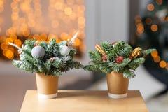 Två pappers- kaffekoppar för hantverk på en trätabell Begreppet av julkaffe med garneringgranträdet på Royaltyfri Fotografi