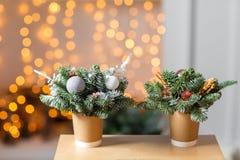 Två pappers- kaffekoppar för hantverk på en trätabell Begreppet av julkaffe med garneringgranträdet på Royaltyfri Foto