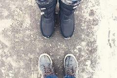 Två par av ben som bär vinterskor, står mitt emot de på den snöig vägen royaltyfri bild