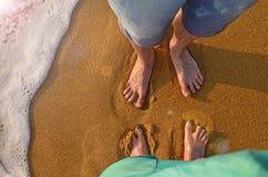 Två par av fot står på sanden och väntar på vågen för att komma vinka på den sandiga stranden av Kalutara, Sri Lanka Arkivbilder