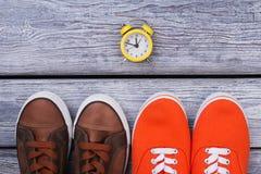 Två par av skor och klockan Arkivbild