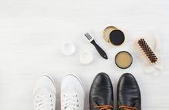 Två par av skor, skokräm och borsten på vit Arkivbilder